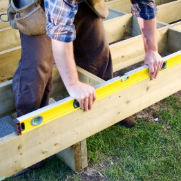 Carpenter checking level of deck boards