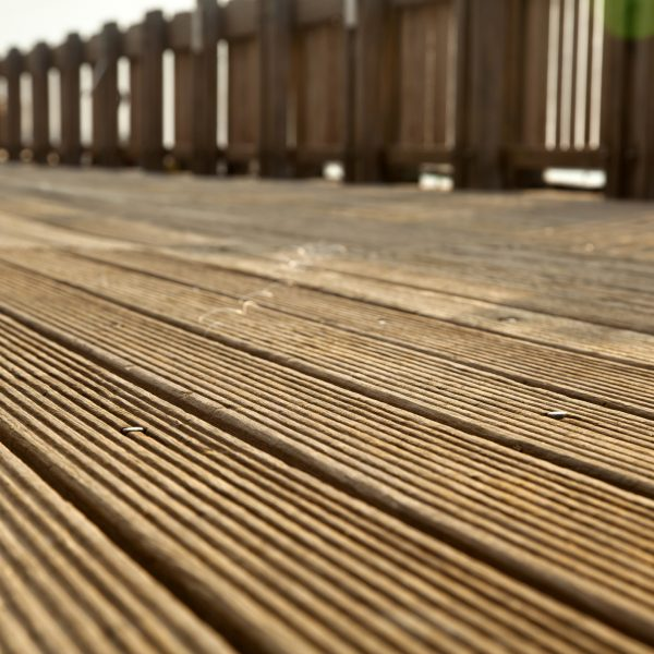 A wooden deck footpath in the sunlight, diminishing perspective.